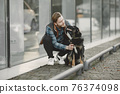 Man with a dog in a city 76374098