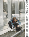 Man with a dog in a city 76374099