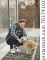 Man with a dog in a city 76374102