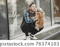 Man with a dog in a city 76374103