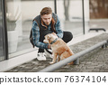 Man with a dog in a city 76374104