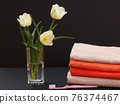 Bouquet of yellow tulips in vase with towels on a black background. 76374467