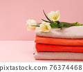 Bouquet of yellow tulips with towels on a pink background. 76374468