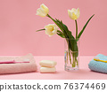 Bouquet of yellow tulips in vase with towels on a pink background. 76374469
