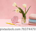 Bouquet of yellow tulips in vase with towels on a pink background. 76374470