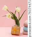 Bouquet of yellow tulips in vase with towels on a pink background. 76374471