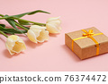 Gift box with tulip flowers on a pink background. 76374472
