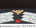 Wooden lotto barrels with game cards and red chips on black background. 76374475