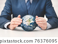 Businessman in suit protects the planet earth 76376095