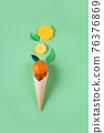 Waffle cone with paper fruits on green background. 76376869