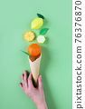 Hnd holding waffle cone with paper fruits 76376870