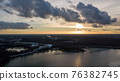 Aerial view of a beautiful and dramatic sunset over a forest lake reflected in the water, landscape 76382745