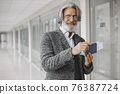 Senior businessman with travel suitcase in airport 76387724