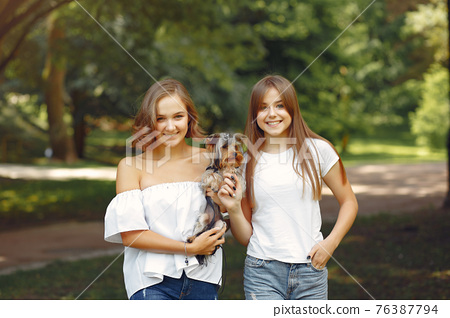 Two cute girls in a park playing with little dog 76387794