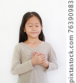 Asian little girl closed eyes and holding hands on heart gesture of love. Kid place arms on chest 76390983