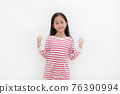 Cheerful Asian little child on white. Kid raising hands up and strong gesture. Good health concept 76390994