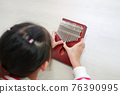 Close-up Asian young hands playing Kalimba (Mbira or thumb piano) lying on wood floor at home. 76390995