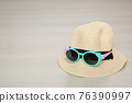 Summer hat with sunglasses on wooden laminate flooring background 76390997