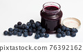 Ripe bilberries and jar of blueberry jam 76392162