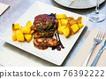 Baked sirloin medallion with potato at white plate 76392222