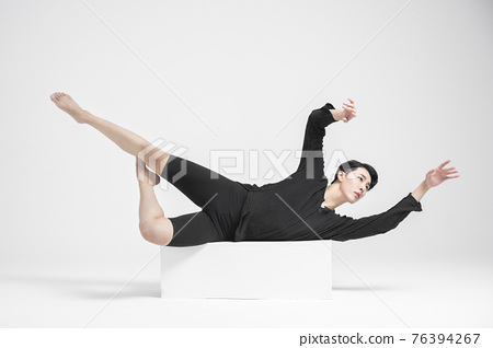 contemporary asian male dancer making move in white background 76394267