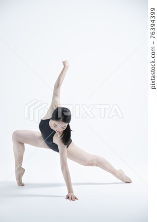 contemporary Asian female dancer making move in white background 76394399