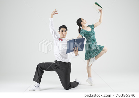 Asian couple contemporary dancers holding book 76395540