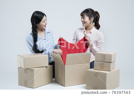 two Asian women, sisters unboxing delivery box on floor 76397563