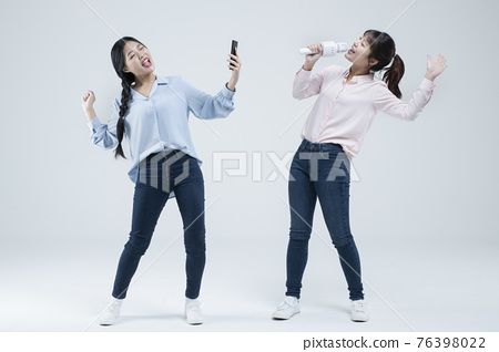 two Asian women, sisters singing with wireless mic and mobile karaoke application on phone 76398022