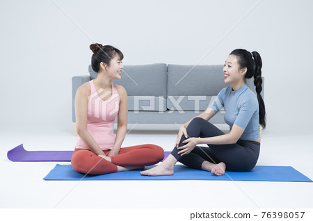 two fit Asian young women home training concept wearing sports top and leggings 76398057