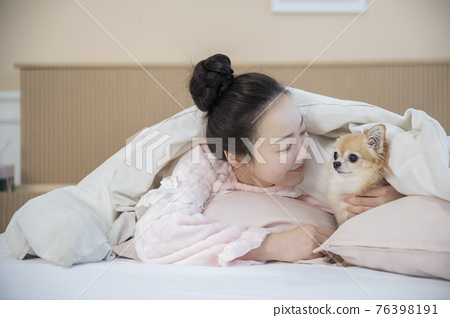 Asian woman in pajamas under blanket hugging puppy dog 76398191