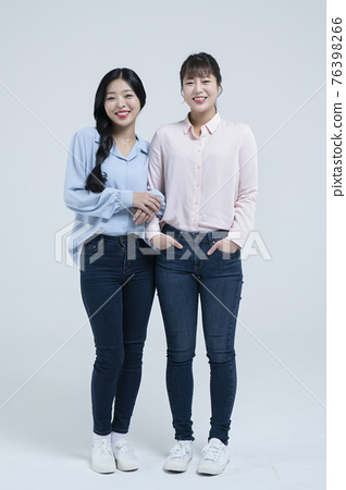 Smiling beautiful Asian woman holding arm of sister 76398266