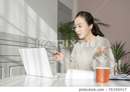 remote work, working at home concept of Asian woman with hair tied back and wearing sweater 76398417