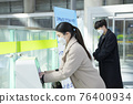 Asian man and woman sanitizing hands, train station 76400934