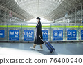 Asian man and woman with masks, carrying carrier in train station 76400940