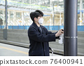 Asian man with masks sanitizing hand in train station 76400941