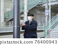 Asian man with masks sanitizing hand in train station 76400943