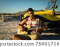 Happy caucasian man leaning against beach buggy by the sea playing guitar 76401714