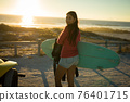 Happy caucasian woman on the beach carrying surfboard during sunset 76401715