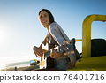 Happy caucasian woman sitting on beach buggy by the sea playing guitar 76401716