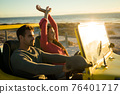 Happy caucasian couple sitting in beach buggy by the sea during sunset 76401717