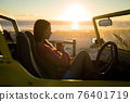 Caucasian woman sitting in beach buggy by the sea during sunset 76401719