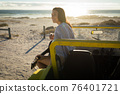 Happy caucasian woman sitting on beach buggy by the sea playing guitar 76401721
