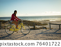 Happy caucasian woman on the beach riding bicycle 76401722