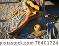 Low section of caucasian woman sitting on beach by the sea playing guitar 76401724
