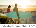 Caucasian couple on the beach carrying surfboard during sunset 76401725