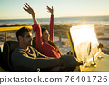 Happy caucasian couple sitting in beach buggy by the sea during sunset 76401726