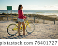 Happy caucasian woman on the beach with bicycle looking toward sea 76401727