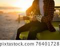 Midsection of caucasian man sitting on beach buggy by the sea playing guitar during sunset 76401728