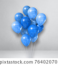 Blue balloons bunch on a white wall background 76402070